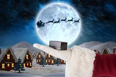 Hand of santa claus holding gift box Stock Images