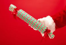 Hand of Santa Claus holding a gift on red background stock image