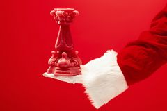 Hand of Santa Claus holding a toy Christmas candle on red background royalty free stock photography