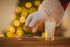 Hand of santa claus picking cookie Royalty Free Stock Image