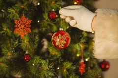 Hand of santa hanging a bauble Royalty Free Stock Photos