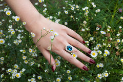 Hand with sapphire ring. In the flowers Royalty Free Stock Image