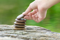 Hand satt sten som bygger en hög av zenstenar Arkivfoto