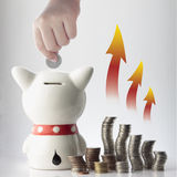 A hand saving coin in piggy bank Stock Image