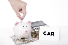 Hand saving money in piggy bank for message car. royalty free stock photos