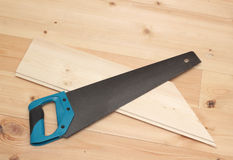 Hand saw and cutted deal board Stock Photo