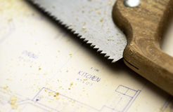 Hand saw lying on blueprints Stock Photos