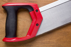 Hand saw with a red handle Stock Images