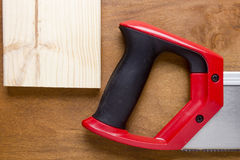 Hand saw with a red handle Royalty Free Stock Images