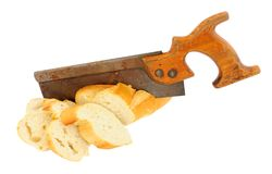 Hand Saw Sawing A Crusty Bread Baguette. Old wooden handled saw sawing a crusty bread baguette isolated on a white background stock images