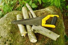 Hand-saw y leña Imágenes de archivo libres de regalías