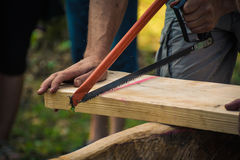 Hand sawing wooden plank. Or board Royalty Free Stock Photo