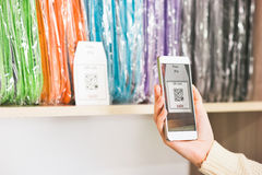Hand scanning qr code with smartphone on showcase Stock Images