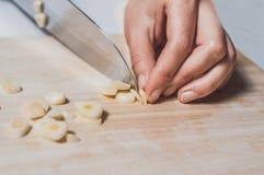Hand scherp knoflook op houten bureau Royalty-vrije Stock Foto