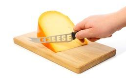 Hand schneidet mit Messer den Käse auf einem Schneidebrett Stockbild