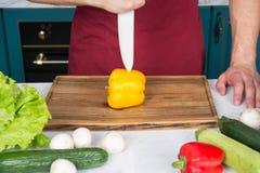 Hand schnitt gelben Pfeffer mit Messer auf hölzernem Schneidebrett Stockfotos