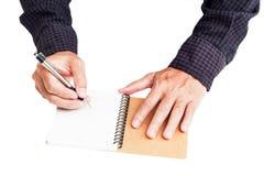 Hand schreiben auf das Notizbuch Lizenzfreie Stockfotos