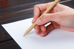 Hand schreibt auf eine weiße Liste des Papiers mit einer Stiftzusammensetzung Hohes Design des Spotts Stockfotografie