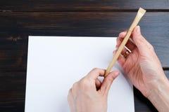 Hand schreibt auf eine weiße Liste des Papiers mit einer Stiftzusammensetzung Hohes Design des Spotts Lizenzfreie Stockfotos