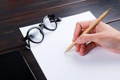 Hand schreibt auf eine weiße Liste des Papiers mit einer Stiftzusammensetzung Hohes Design des Spotts Stockbild
