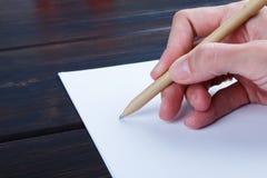 Hand schreibt auf eine weiße Liste des Papiers mit einer Stiftzusammensetzung Hohes Design des Spotts Stockfoto