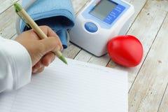 Hand schreibt auf leeres leeres Papier mit Blutdruck-Monitormeter und Herzformsymbol auf Holztisch Stockfotos