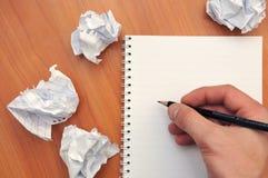 Hand schreibt in ein Notizbuch um ein zerknittertes Papier lizenzfreie stockfotografie
