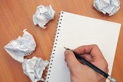 Hand schreibt in ein Notizbuch um ein zerknittertes Papier lizenzfreie stockfotos