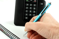 Hand schreibt eine Feder auf ein Notizbuch Lizenzfreie Stockfotografie