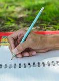 Hand schreibt einen Stift in ein Notizbuch Lizenzfreie Stockbilder