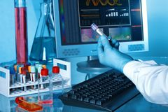 Hand of scientist with blood tube and computer in the lab royalty free stock photo