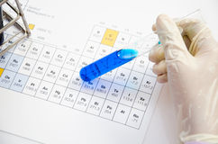 Hand scientist hold test tubes medical glassware on periodic tab Stock Photo