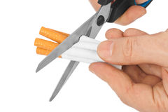 Hand with scissors and cigarettes Royalty Free Stock Photos