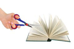Hand with scissors cutting book Royalty Free Stock Photo