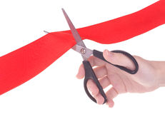 Hand with scissors cutting red ribbon Royalty Free Stock Photography