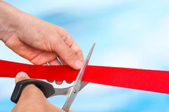 Hand with scissors cutting red ribbon - opening ceremony Royalty Free Stock Images