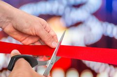 Hand with scissors cutting red ribbon - opening ceremony Stock Image