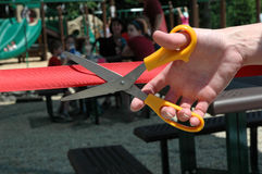 Hand and scissors cutting a ribbon during an opening ceremony Stock Photo
