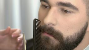 Hand with scissors trimming beard. Handsome bearded face, close up stock video