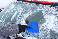 Hand scraping ice from the car window Royalty Free Stock Photos