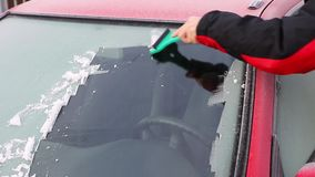 Hand is scraping ice from the windshield of the car stock footage
