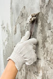 Hand scraping off old wet wallpaper with spatula Stock Photography