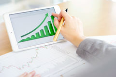 Hand on screen tablet pc with business information Stock Image