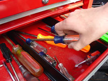Hand and Screwdriver. A hand is picking up a screwdriver from a toolbox stock images