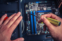 Hand with screwdriver installing computer Stock Image