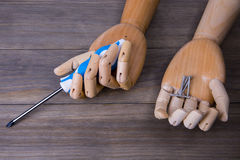 Hand with a screwdriver and some screws. Hand with a screwdriver on a wooden background Royalty Free Stock Photography
