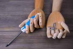 Hand with a screwdriver and some screws. Hand with a screwdriver on a wooden background Stock Images