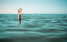 Hand in sea water asking for help. Failure and Stock Photo