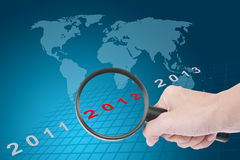 Hand searching new year 2012 with world map. As a background Stock Photos