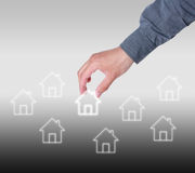 Hand select home symbol. On gray gradually varied background. Real estate concept Stock Photos